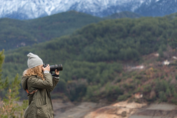 Photographer woman shooting winter landscape in mountains