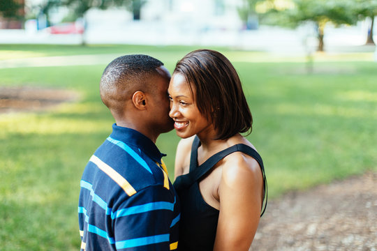 African-American male whispering into his girlfriend's ear