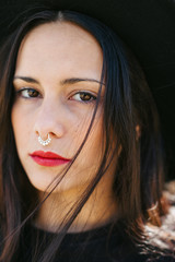 Portrait of a young alternative woman with a nose ring and red lips.