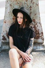 Young alternative woman with tattoos sitting on the street.