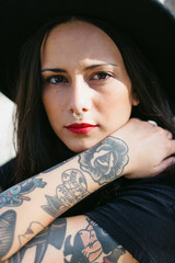 Portrait of an alternative woman with tattooed arm and nose ring looking at camera.