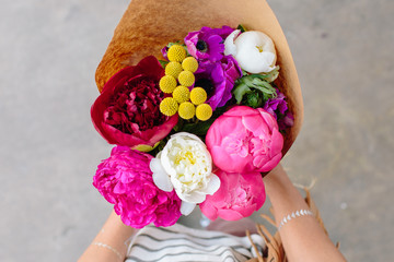 Someone holding a vibrant flower arrangement from the flower market