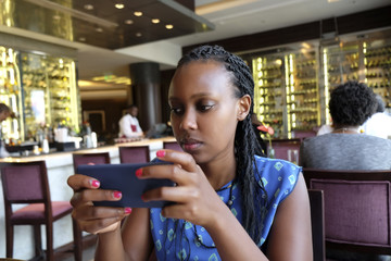 Young woman checking phone in a bar