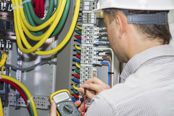Engineer tests supply circuit in powerful panel of distribution cables on terminal box background. Electrician with multimeter measures voltage in fuse box