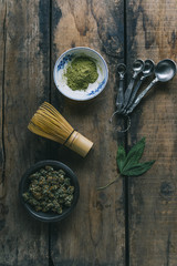 Overhead view of cannabis, leaf, whisk measuring spoons on wooden table