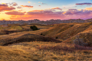 The sun sets over the golden fields of Badlands National Park, South Dakota