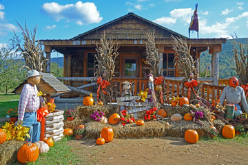 Fall decorations around an old log building.