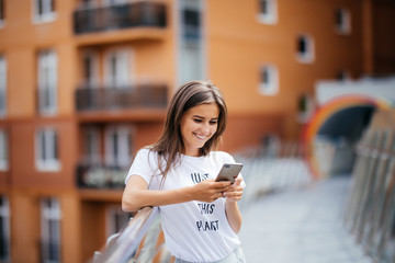 Lifestyle portrait of a woman dressed casually standing with phone on the modern bridge