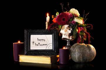 Still life of skull decorated with flowers, burning candles and a pumpkin on black with happy halloween card in a frame