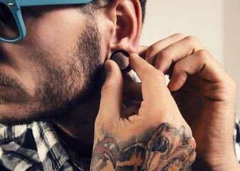 Closeup shot of hipster earring, man placing/ putting gauge earring