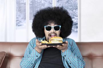 Funny Afro man eating a cheeseburger