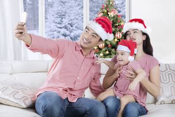 Cheerful family taking selfie at Christmas time