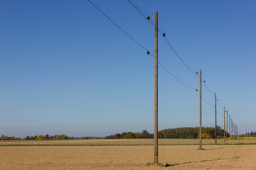 telegraph pole beside a bikeway and white tower on a plain field and wide horizon view