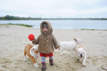 The crying baby girl and puppies of a bulldog play in the beach in the autumn