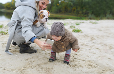 Happy mother and baby girl with her puppy making selfie outdoors