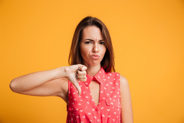 Young upset brunette woman showing thumb down gesture, looking at camera