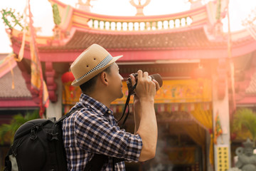 Tourist sightseeing old town, travel concept..Street photographer taking a picture of old shrine chinese temple in phuket old town with vintage camera ,side view.
