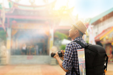Tourist sightseeing old town, travel concept.Street photographer wandering to old shrine chinese temple in phuket old town,side view.