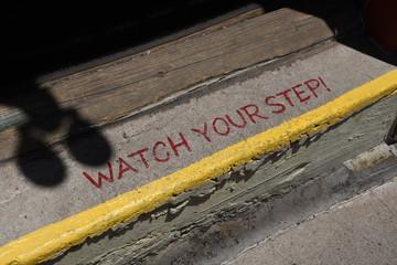"""Treppenstufe mit englischer Aufschrift, übersetzt: """"Vorsicht, Stufe"""""""