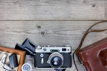 empty photo frame, old camera with leather case and negative films on wooden background