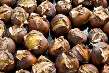 Group of freshly roasted chestnuts in baking pan.