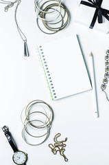 Women's jewelry and note books on white background