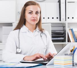 Doctor in uniform is working behind laptop