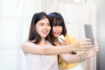 Portrait a beautiful asian teen woman smiling,happy,fun and selfie with her smartphone