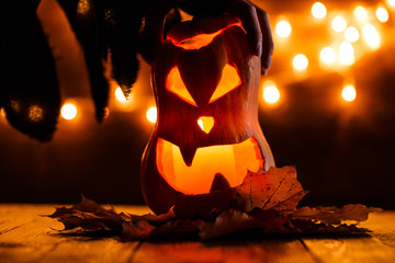 Photo of halloween pumpkin cut in shape of face with witch's hand