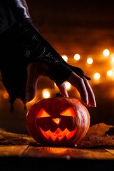 Image of halloween background with pumpkin and witch hand