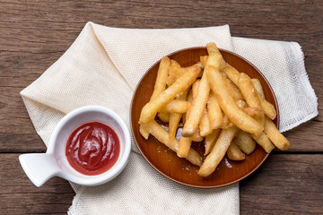The french fries are placed in a cup with ketchup.