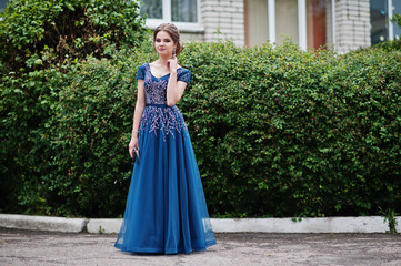 Portrait of a beautiful and gentle girl in elegant gown posing outdoor.