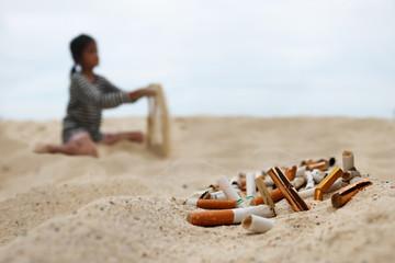 Cigarette and tobacco ashtray on the beach