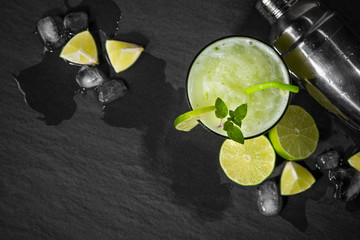 Cocktail juice with lime, mint and ice. Bar drink accessories on black table background.