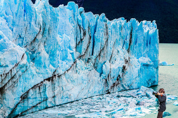 Woman photographs the blue ice wall