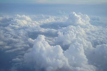 Fototapeta View of beautiful heaven cloudscape with shades of blue sky background from flying plane window