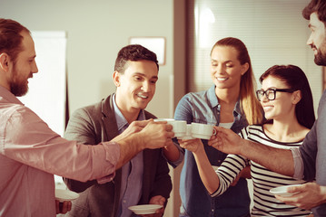 Happy delighted colleagues holding coffee cups