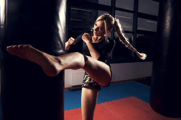 Gorgeous female fighter with blonde hair pulled back in long braid, dressed in black crop top and camouflage shorts, hitting punching bag with her leg. Attractive young woman training in sports club.