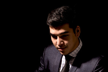 Portrait of young businessman on dark background