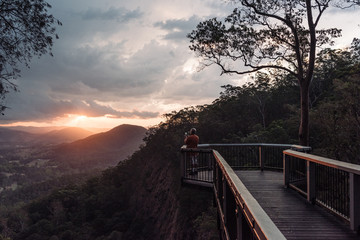 Man takes image of sunset over bush valley from lookout point