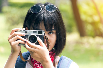 Asian woman taking picture with camera
