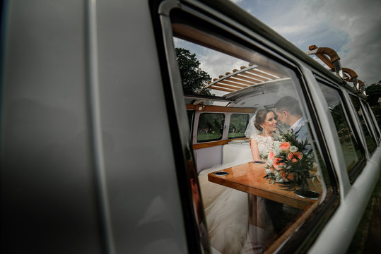 Tender young wedding couple poses in an old bus