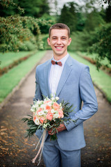 Handsome groom in grey suit stands with pink bouquet in the park