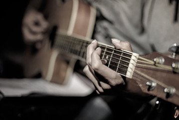 Close-up man playing acoustic guitar