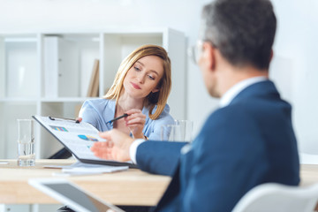 businesswoman giving documents to partner