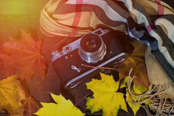 Vintage camera on a wooden table with autumn leaves and a scarf. Autumn theme