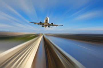Airliner over highway on blurred background