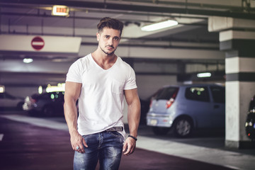 Handsome muscular man in casual clothing looking at camera on background of parking.  Wall mural