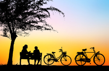 silhouette vintage bike and love couple in  the holiday on blurry sunrise time