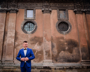 Happy groom in blue suit stands before an old wall of the cathedral